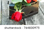 Small photo of The rose red and old iron on the old table/ fresh rose amid old iron/red delicate flower and decrepitude