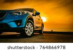 Stock photo blue compact suv car with sport and modern design parked on concrete road by the sea at sunset 764866978