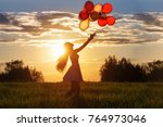 girl with balloons at sunset   Shutterstock . vector #764973046