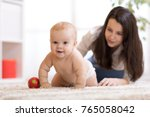 mother playing with creeping on ... | Shutterstock . vector #765058042