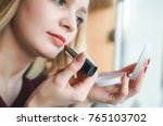 pretty girl paints lips with... | Shutterstock . vector #765103702