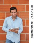 Small photo of Attractive man using electronic tablet leant on brickwall