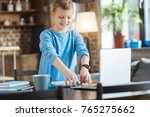 Small photo of Smart schoolchild. Positive nice delighted boy standing near the table and smiling while looking at his copybook