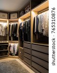 Small photo of Luxurious walk in closet with lighting and jewelry display.