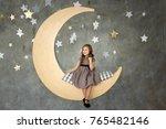 little girl in gray dress is... | Shutterstock . vector #765482146