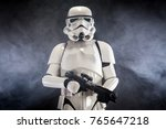 Small photo of SAN BENEDETTO DEL TRONTO, ITALY. NOVEMBER 11, 2017. Studio portrait of stormtrooper costume replica, with blaster E-11 gun. He is a fictional character of Star Wars saga. Black background with smoke