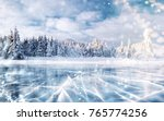 Small photo of Blue ice and cracks on the surface of the ice. Frozen lake in winter mountains. It is snowing. The hills of pines. Winter. Carpathian Ukraine Europe.