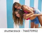 best friends girls piggyback in ... | Shutterstock . vector #766070902