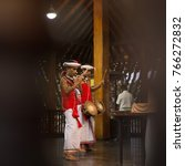 Small photo of Colombo, Sri Lanka - January 18, 2017 : Two Kandian dancers drummer and fluter playing Tammattama drum and flute in temple wearing red.
