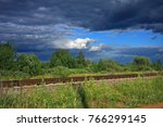 Small photo of Railroad tracks form the border between the storm cloud and sunlight in the distance one can see green trees and bushes in the foreground green grass in the center of the clouds like an island of clea