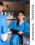 Small photo of smiling Asian paramedic sitting in ambulance and looking at camera