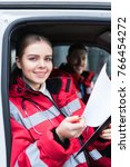 Small photo of smiling young female paramedic holding clipboard and looking at camera