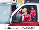 handsome male paramedic talking ...