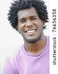 portrait of young african american guy looking at camera near the sea. Vertical shape, head and shoulders - stock photo