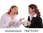 Two women with headsets on taking a break drinking coffee, isolated on white background. - stock photo
