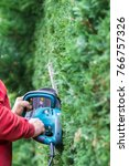 man is hedge trimming with... | Shutterstock . vector #766757326