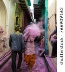 Small photo of People sitting on the street in the villages of Barsa and Mathura India during the holi festivals days and are covered with powder in all different colors especially pink and red