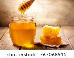 jar of honey with honeycomb on... | Shutterstock . vector #767068915