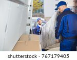 two happy male movers in... | Shutterstock . vector #767179405