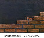 Small photo of FEAR word on the black background with wall brick. the concept of state of mind