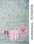 Small photo of Children's bib, dress and red shoes for the girl, dry on a rope on a white brick wall.