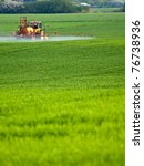 Tractor Spraying A Green Field...