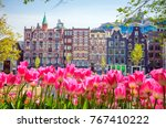 Small photo of Traditional old buildings and tulips in Amsterdam, Netherlands
