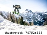 Snoboarder performing tricks on the snow - stock photo