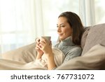 Small photo of relaxed tenant resting holding a coffee mug sitting on a sofa in the living room in a house interior