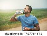 bearded man drinking bottle of... | Shutterstock . vector #767754676