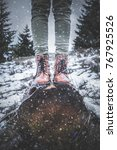 Girl standing on a tree stump in nature with falling snow.