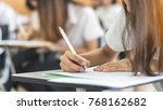 Small photo of School student's taking exam, thinking hard, writing answer in classroom for educational university admission test and world literacy day concept