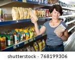 smiling mature woman selecting... | Shutterstock . vector #768199306