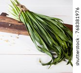 Small photo of Jusai (allium ramosum) on a wooden plate