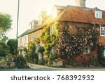 Stock photo old vintage medieval beautiful stone british house with tile roof and bright windows a flowering 768392932