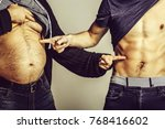 Small photo of Fat belly and muscular torso of two men. Male hands point at torsos of athlete or bodybuilder with abs and six packs and paunch on grey background