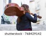 woman carrying acoustic guitar... | Shutterstock . vector #768429142