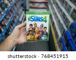 Small photo of Bratislava, Slovakia, december 1, 2017: Man holding The sims 4 videogame on Microsoft XBOX One console in store
