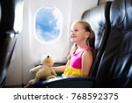 Small photo of Child in airplane. Kid in air plane sitting in window seat. Flight entertainment for kids. Traveling with young children. Kids fly and travel. Family summer vacation. Girl with toy in airplane.