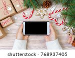 Small photo of Woman using smartphone with blank screen, festive trumpery frame. Christmas gift search, online shopping, seasonal discounts and sale concept.