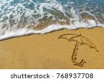 drawing an umbrella on the sand.... | Shutterstock . vector #768937708