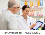 Small photo of medicine, pharmaceutics, healthcare and technology concept - happy apothecary and senior customer with tablet pc computer at pharmacy