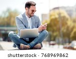 attractive man sitting outside... | Shutterstock . vector #768969862