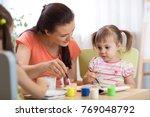 woman teaches children painting ... | Shutterstock . vector #769048792