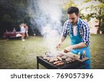 happy male preparing bbq meat | Shutterstock . vector #769057396