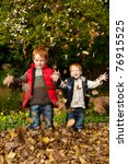 Two smiling brothers / sons are playing in the autumn / fall leaves, throwing them into the air and laughing in a park or garden setting - stock photo