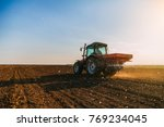 Farmer fertilizing arable land...