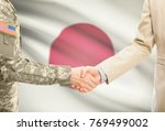 Small photo of American soldier in uniform and civil man in suit shaking hands with adequate national flag on background - Japan
