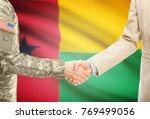 Small photo of American soldier in uniform and civil man in suit shaking hands with adequate national flag on background - Guinea-Bissau