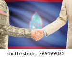 Small photo of American soldier in uniform and civil man in suit shaking hands with adequate national flag on background - Guam